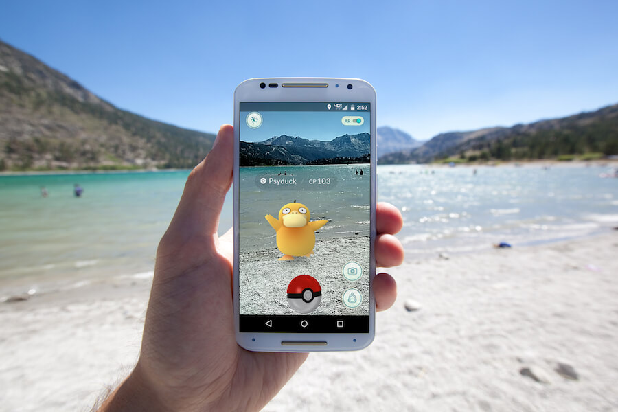 person on the beach playing Pokemon go, person on a beach holding a cell phone