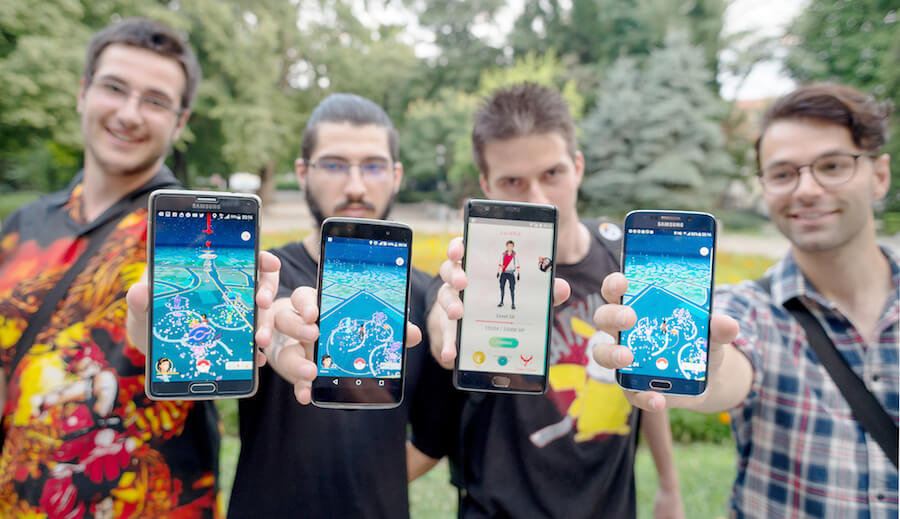 four guys with cell phones, four young guys playing pokemon go,
