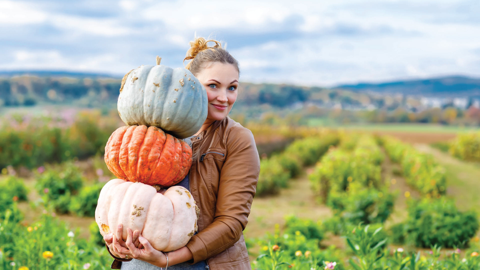Women holding up three pumpkins and smiling at the camera.