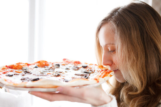 Woman smelling pizza