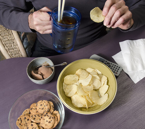 Person eating a lot of junk food, person eating chips, cookies and ice cream