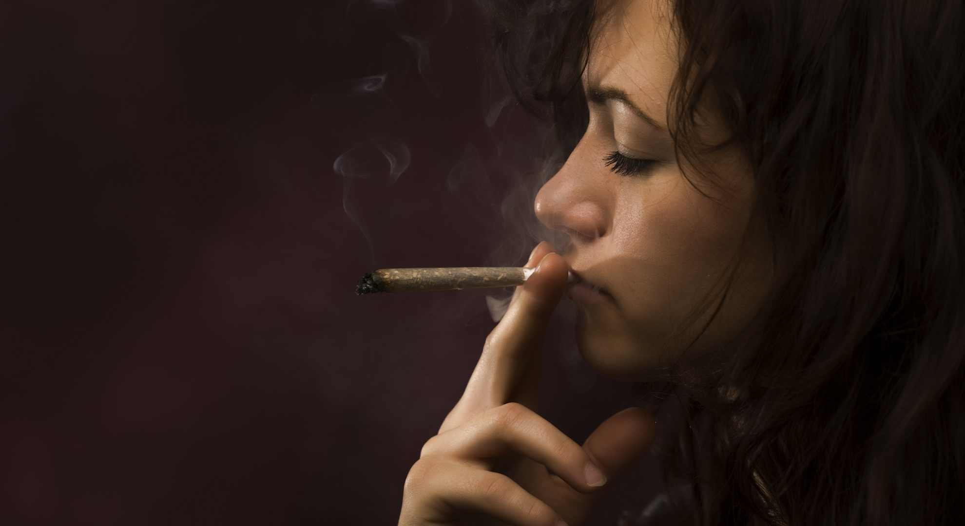 woman inhales from pot joint