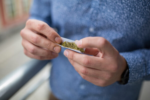 man in sweater rolling a joint
