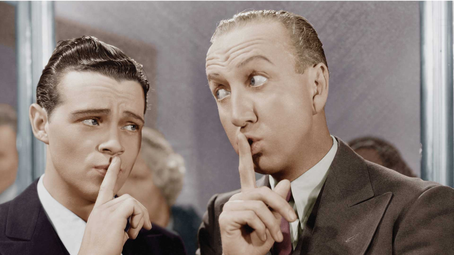 """Two men saying """"Shhhh..."""" to the camera"""