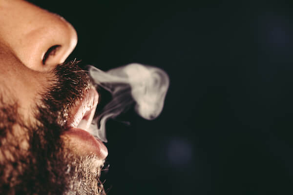 man blowing smoke out of his mouth