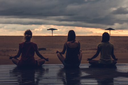 3 women doing yoga on the beach, yoga retreat