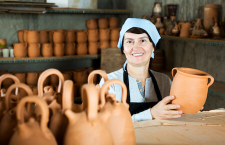 Mature woman holding pottery, craft retreat