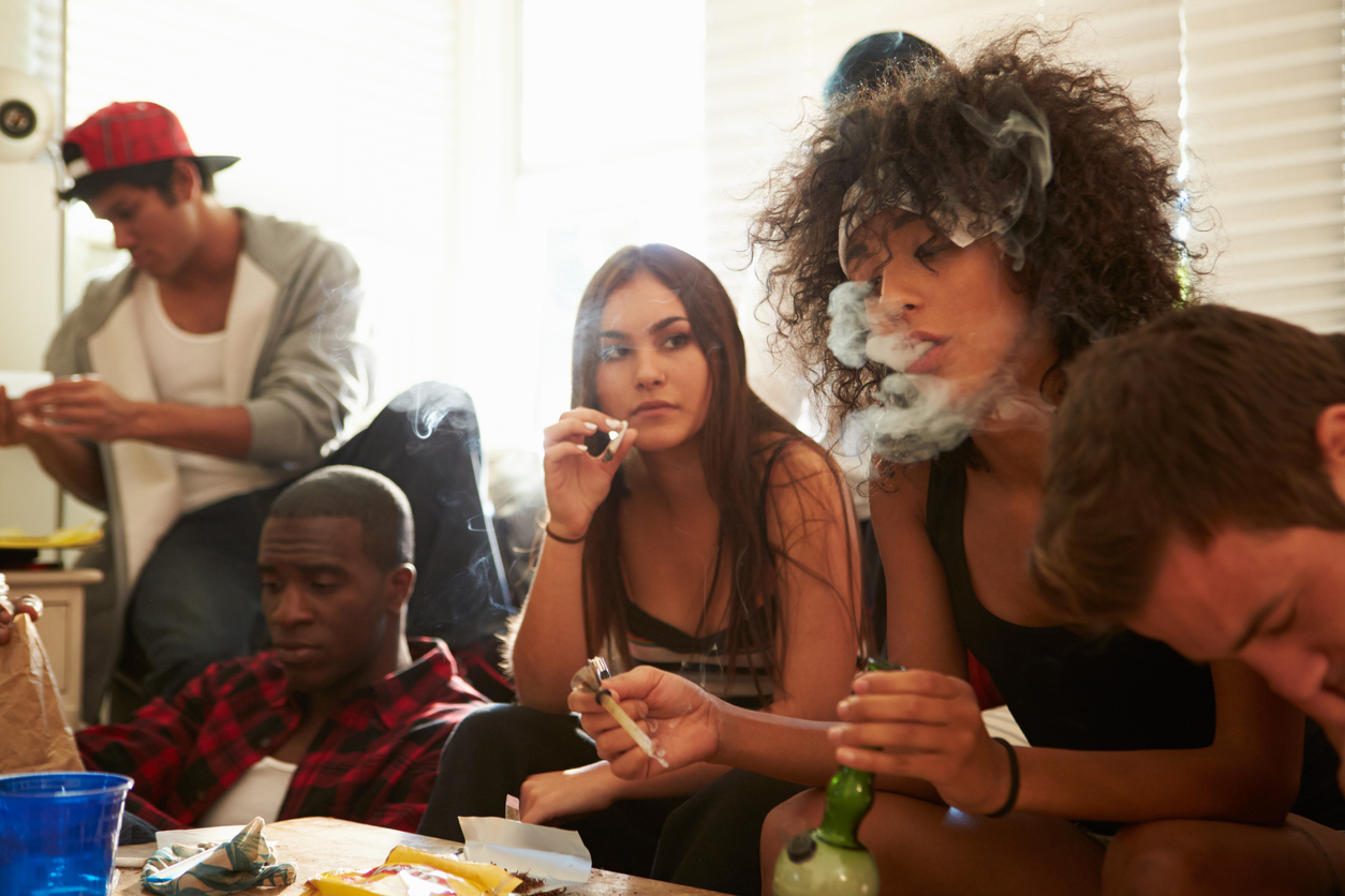 Young People Smoking Weed At Home On Sofa