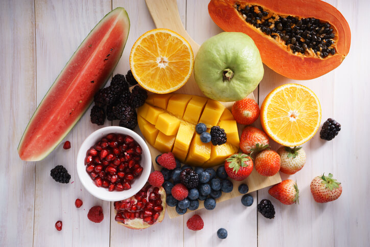 healthy fresh mixed fruits on white wooden table