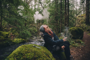 Woman smoking marijuana in the woods.