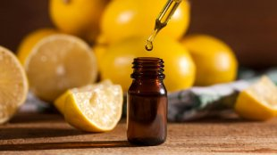 Lemon essential oil and lemon fruits on wooden background
