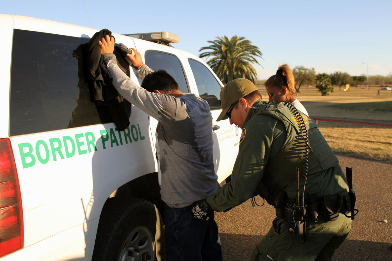 Rio Grande City, Texas, USA - February 9, 2016: A Border Patrol agent takes a Mexican man into custody for illegally entering the U.S. by crossing the Rio Grande River in the Rio Grande Valley in far south Texas. A continuous game of cat and mouse plays out along the river twenty four hours a day.