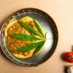 Weed leaf sitting on sausage and eggs in a cooking pot