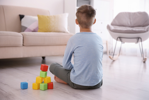 Boy with blocks next to him, autism