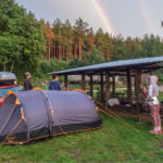 Friends camping under a rainbow