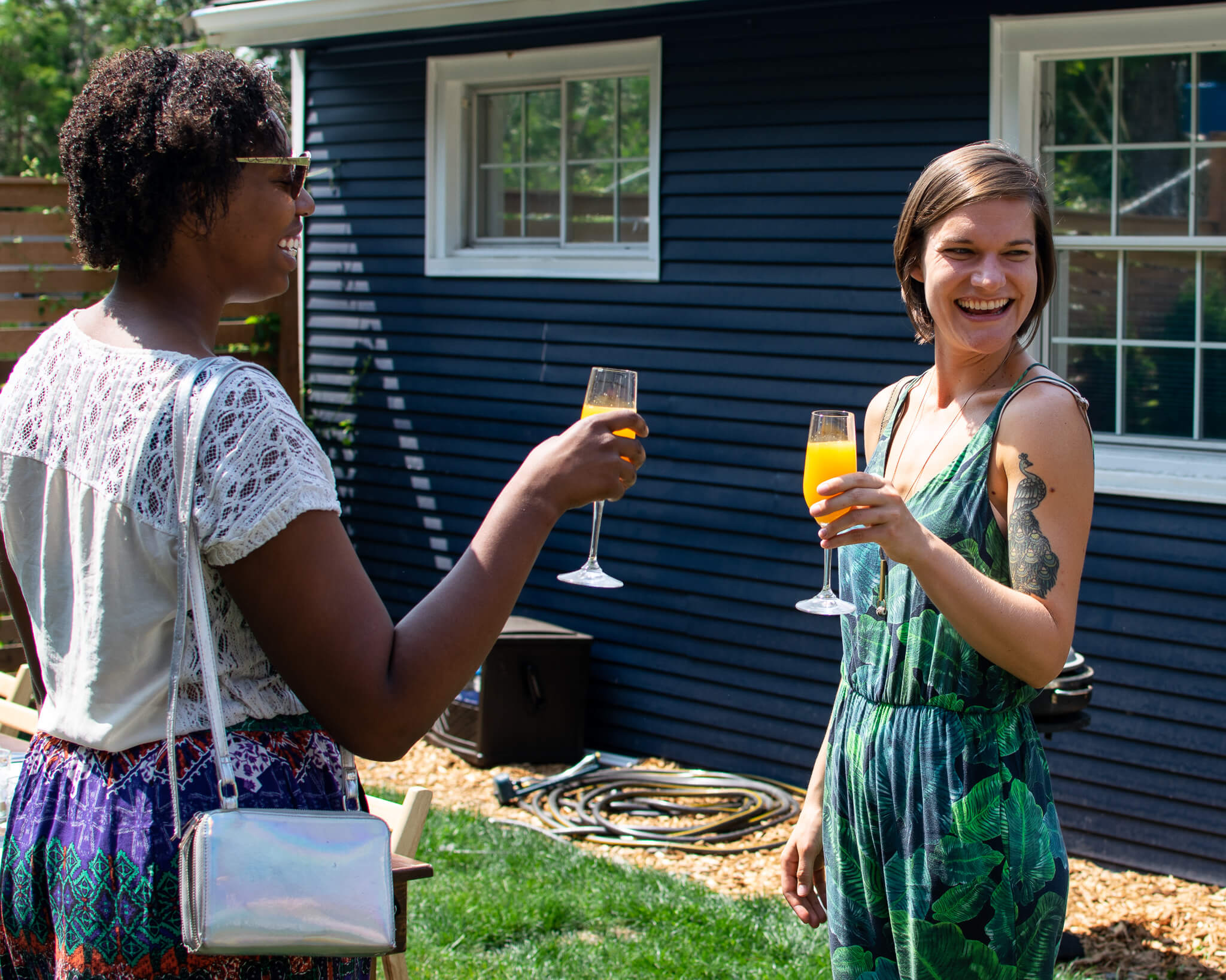 People enjoying conversation and laughing while drinking mimosas.