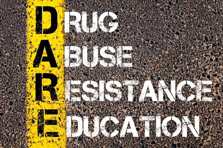 Medical Acronym DARE as DRUG ABUSE RESISTANCE EDUCATION. Yellow paint line on the road against asphalt background. Conceptual image
