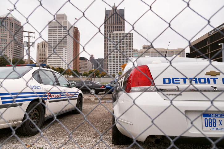 Detroit, MI, USA - October 20, 2014: Police Cars stand on fenced-off ground with Detroit skyscrapers in the background.