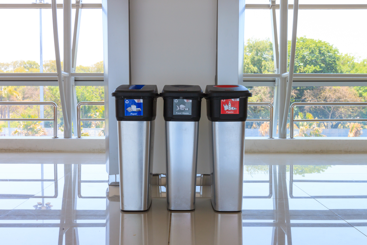 Airport with indicated garbage bins for cans, paper, plastic and other waste.