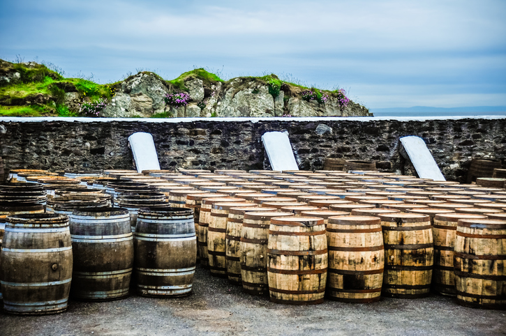 Whisky barrels rest along a wall near the sea on the Isle of Islay, Scotland, United Kingdom