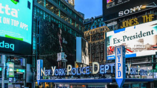 New York Police Department Times Square Precinct against Bright Lights Billboards in Manhattan.