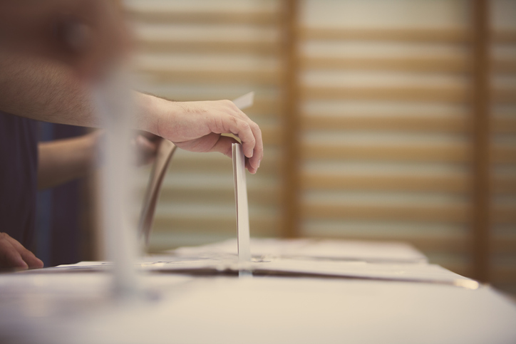 Hand of a person casting a ballot at a polling station during voting.