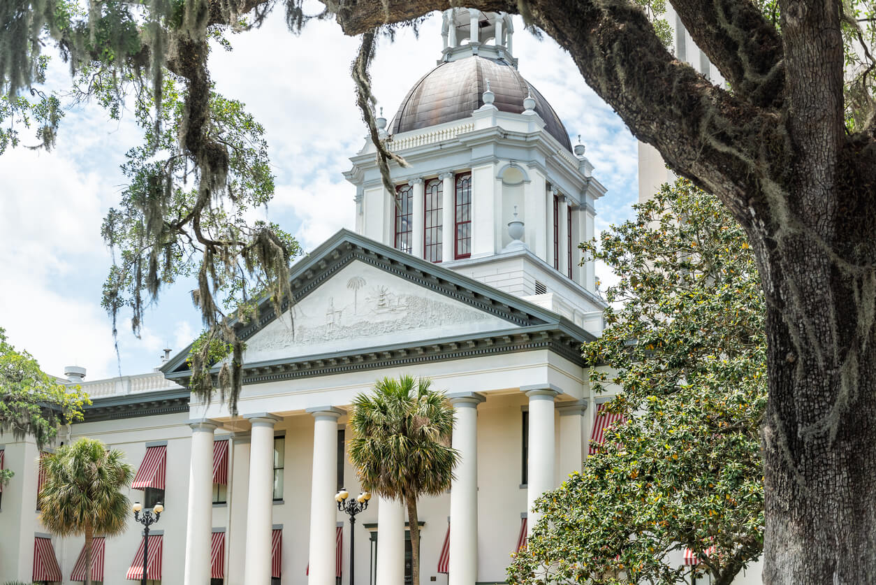 Tallahassee, USA - April 26, 2018: Exterior state capitol building in Florida during sunny day with modern architecture of government, oak tree and spanish moss