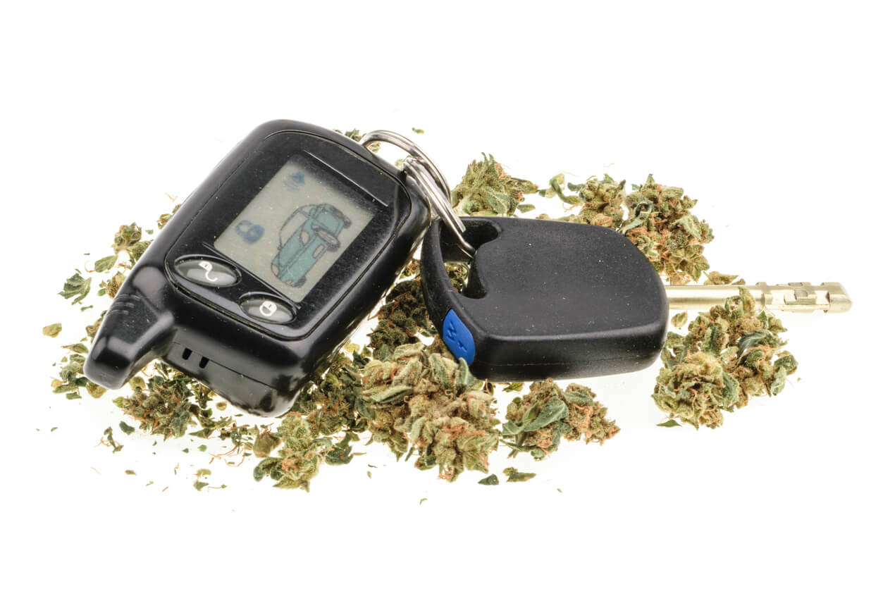 Driving high, marijuana and car key isolated on white