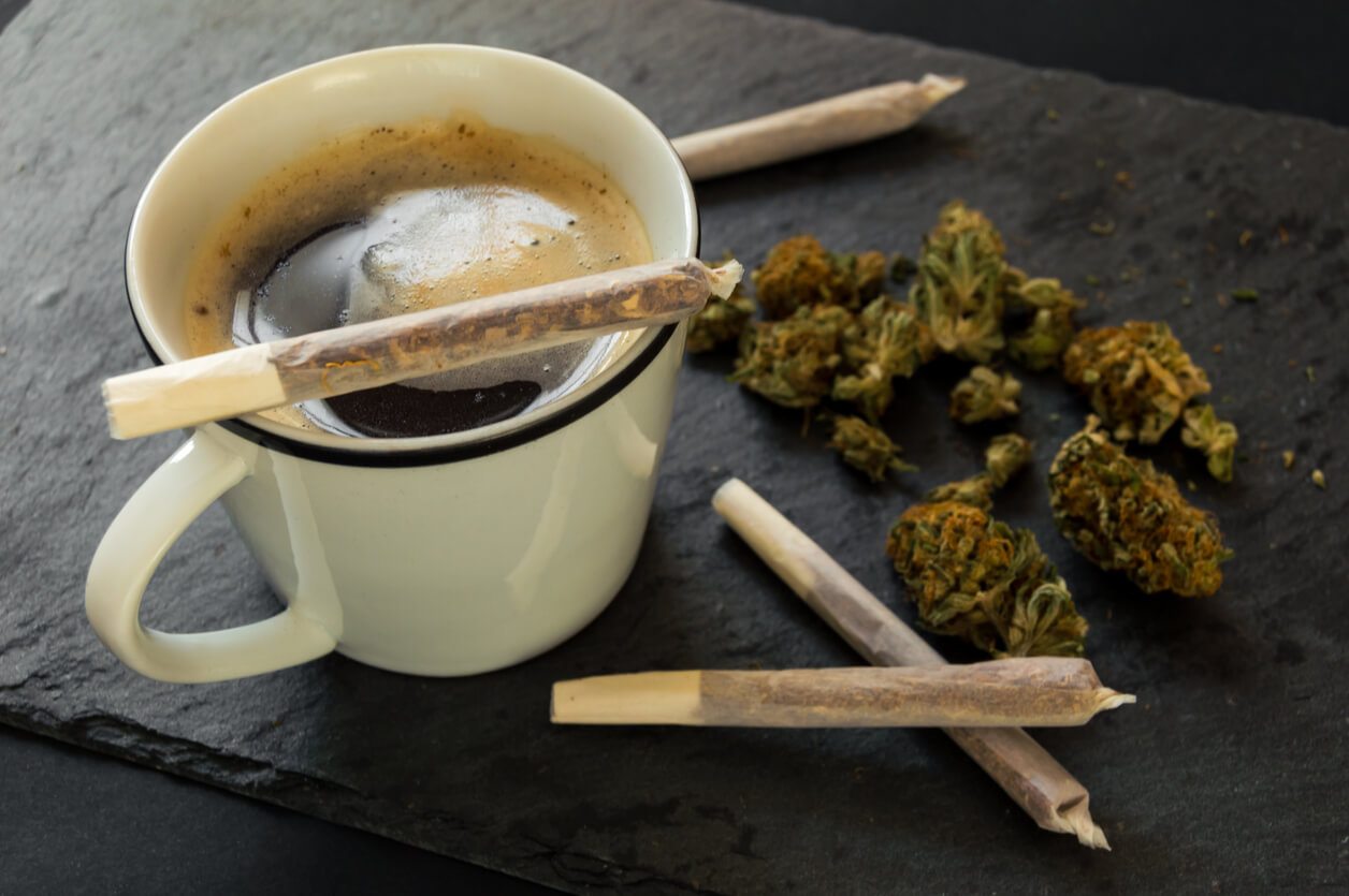 Delicious cup of coffee, a pile of high quality marijuana buds with some cigar of weed ready to smoke. Top view with background of black stone.