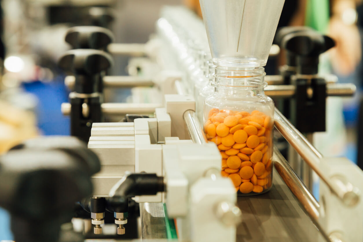 pharmaceutical industry, medicine pills are filling in the plastic bottle on production line machine conveyor at the medical factory. selective focus.