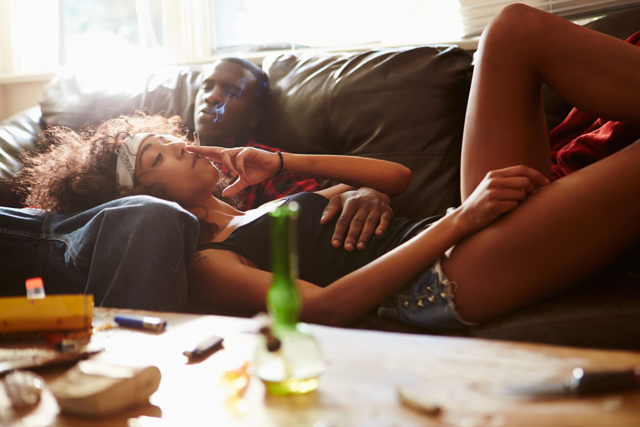 Couple Taking Drugs At Home Together On Sofa