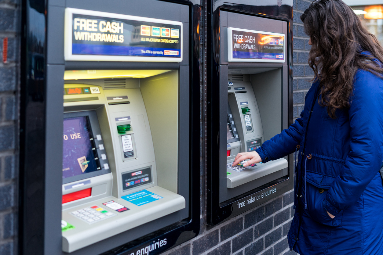 Coventry, UK - NOVEMBER 26, 2016: Young Adult Woman withdrew cash from ATM machine