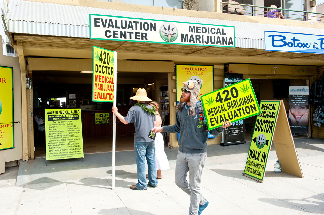 """Venice Beach, USA - March 13, 2011: Employees advertising their services in front of a medical marijuana evaluation center."""
