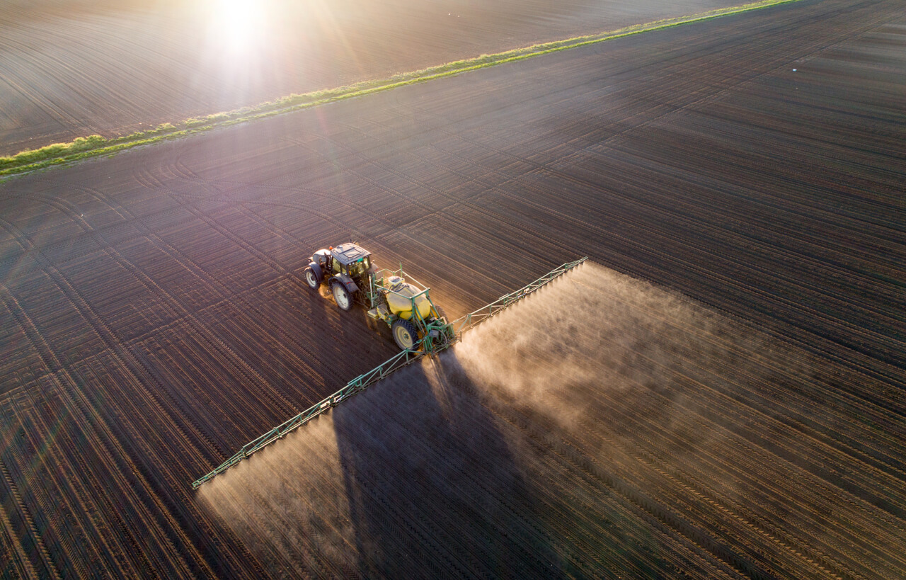 Aerial image of tractor spraying soil and young crop in springtime in field