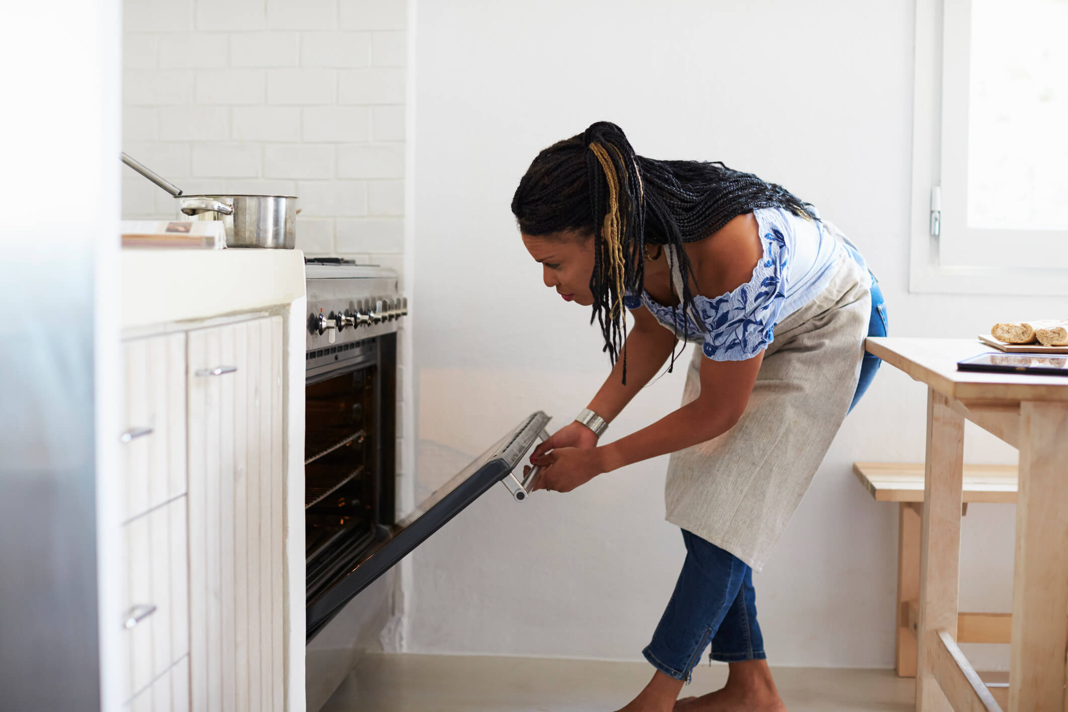 Woman bending down to look into the oven in her kitchen.