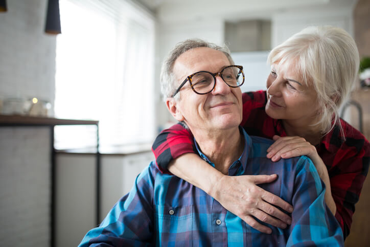 Portrait of happy senior woman embracing her husband
