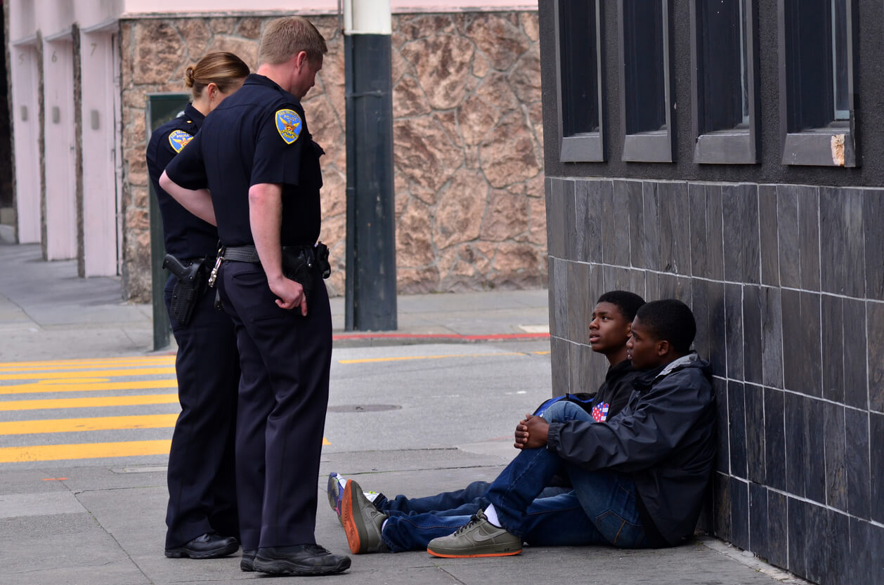 San Francisco, California, USA  - May 19, 2015: SFPD officers interrogating black american men in San Francisco. Overall, Black Americans are arrested at 2.6 times the per-capita rate of all other Americans.