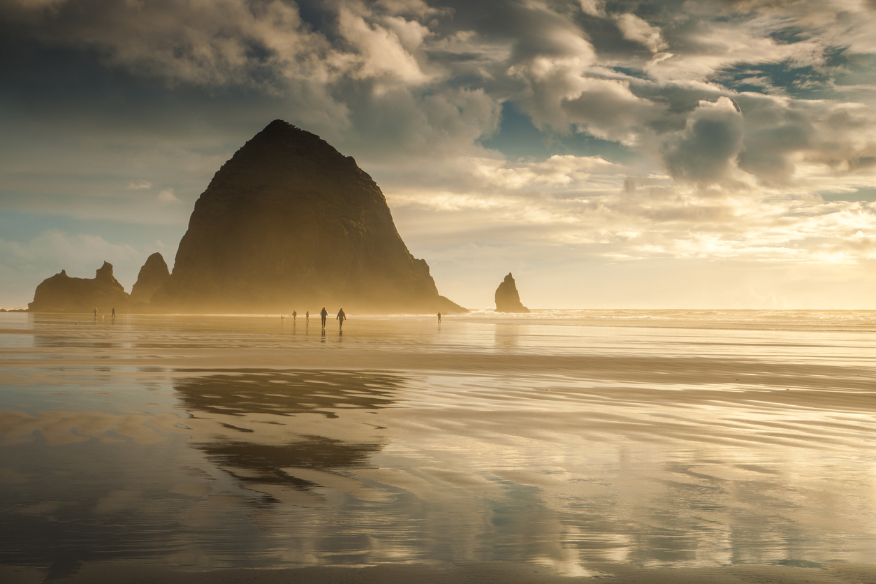 Oregon's Cannon Beach at sunset and in between storms. People can be seen strolling on the beach.