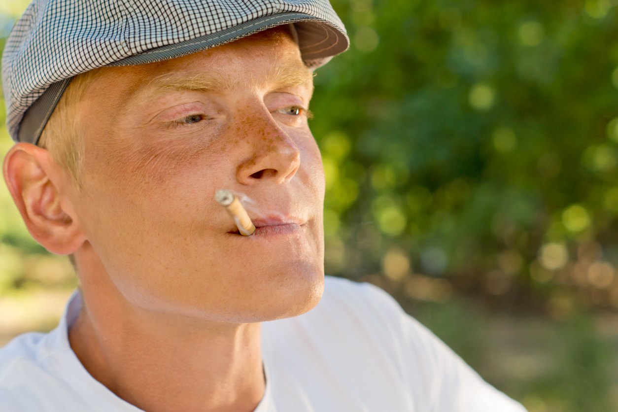 Close-up portrait of a middle-aged thoughtful man smoking recalling good memories, outdoors, in summer