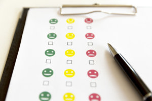 Customer service evaluation survey with smiley faces and pen.