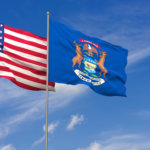 USA and Michigan flags over blue sky background. 3D illustration