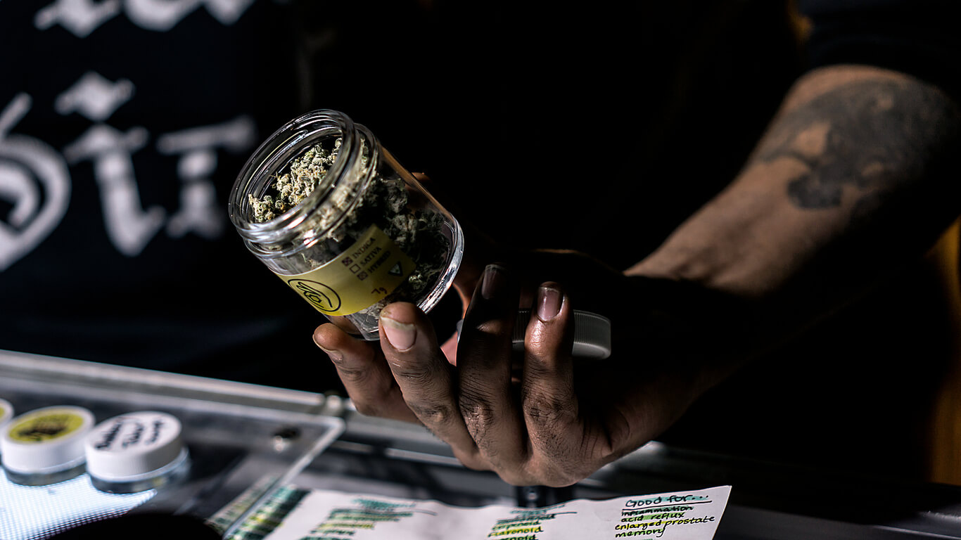 A budtender showing off a jar of cured cannabis flowers.