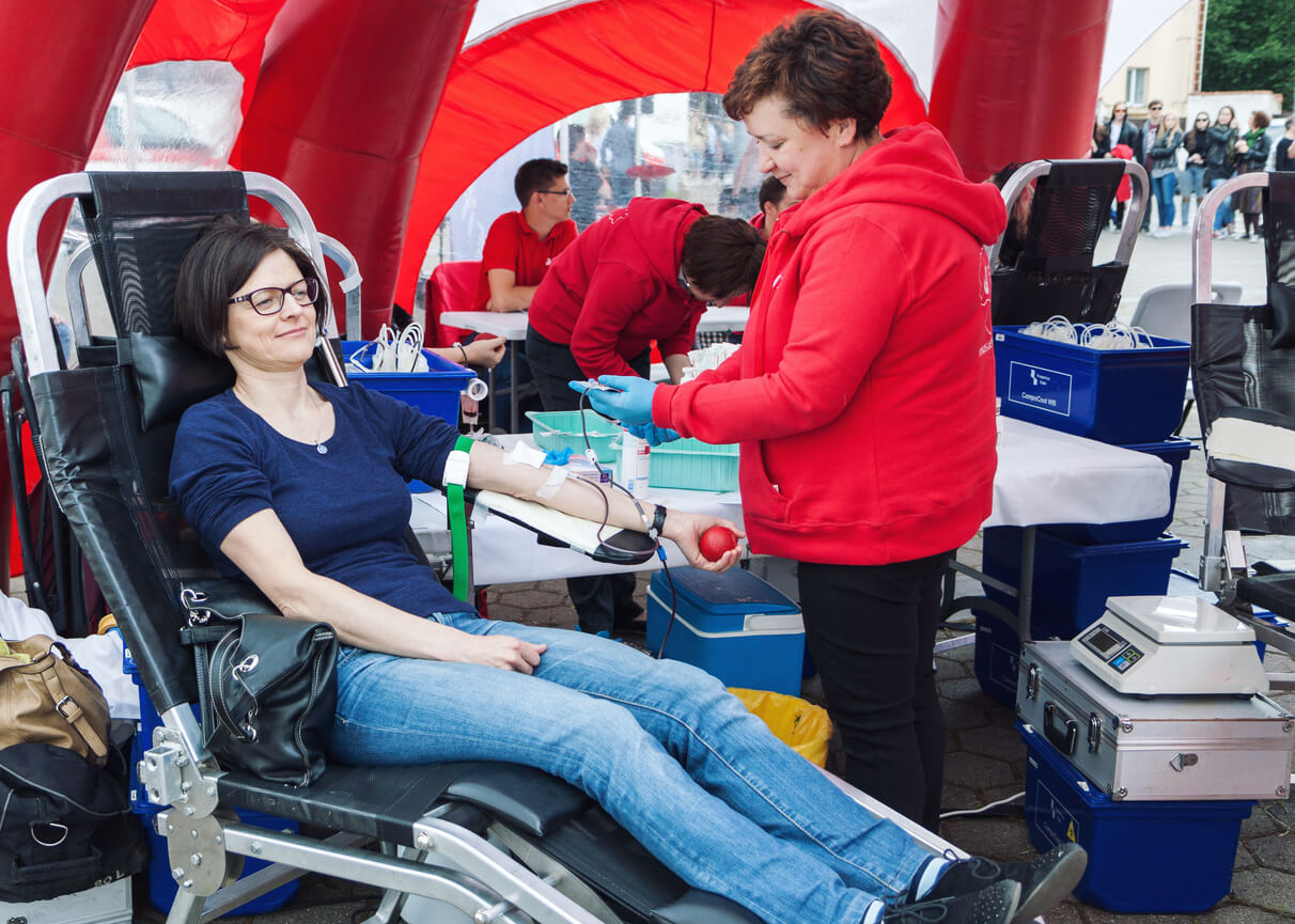 Vilnius, Lithuania - May 21, 2016: Adult middle age woman in care of medicine personnel donating blood in mobile blood donation center on the street of Vilnius, Lithuania.