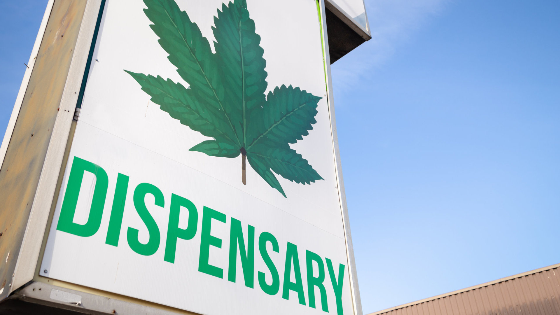 A cannabis dispensary sign with a large marijuana leaf on it