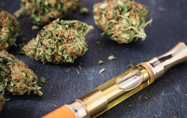 Marijuana buds with a THC oil concentrate filled vape pen