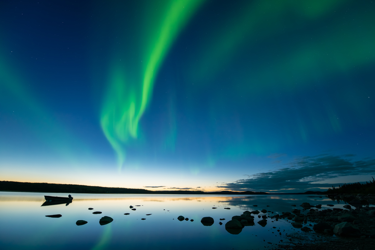 Bands of curvy aurora borealis appear over a northern rocky lake right after sunset.