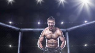 fighter in a mixed fight cage in rage shouting loud