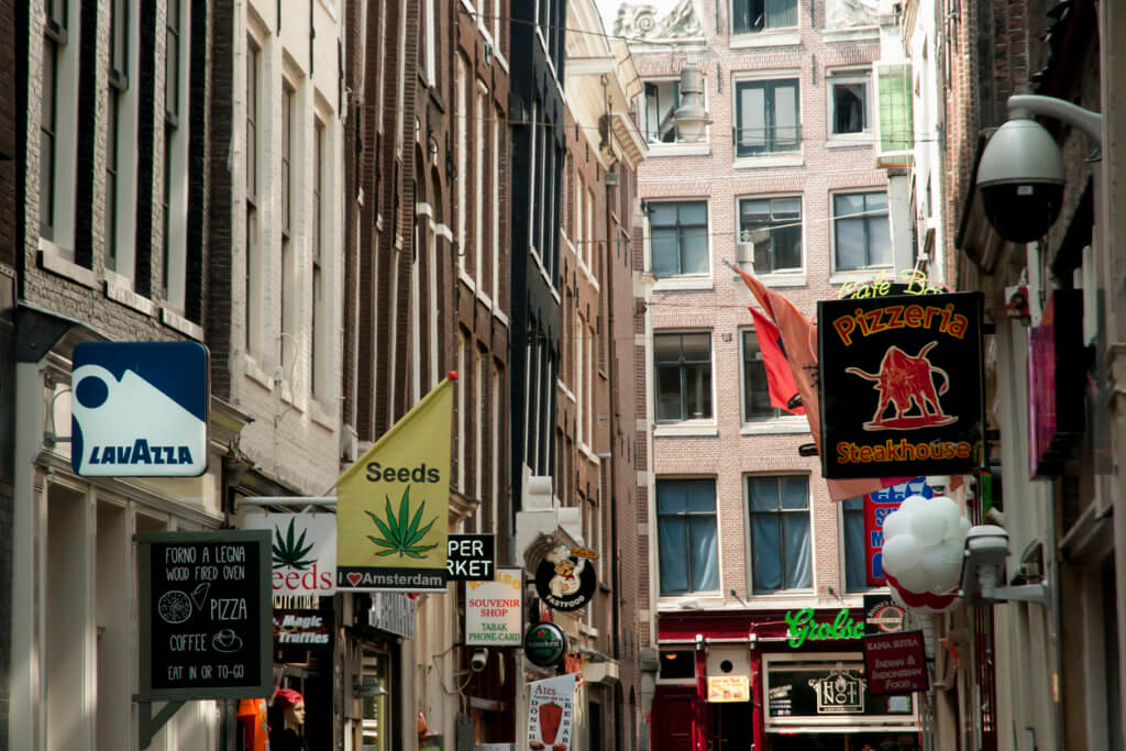 Amsterdam, Netherlands - May 6, 2013: Shop signs in De Wallen alleys of the red light district. Legal drugs can be bought in most of these venues.
