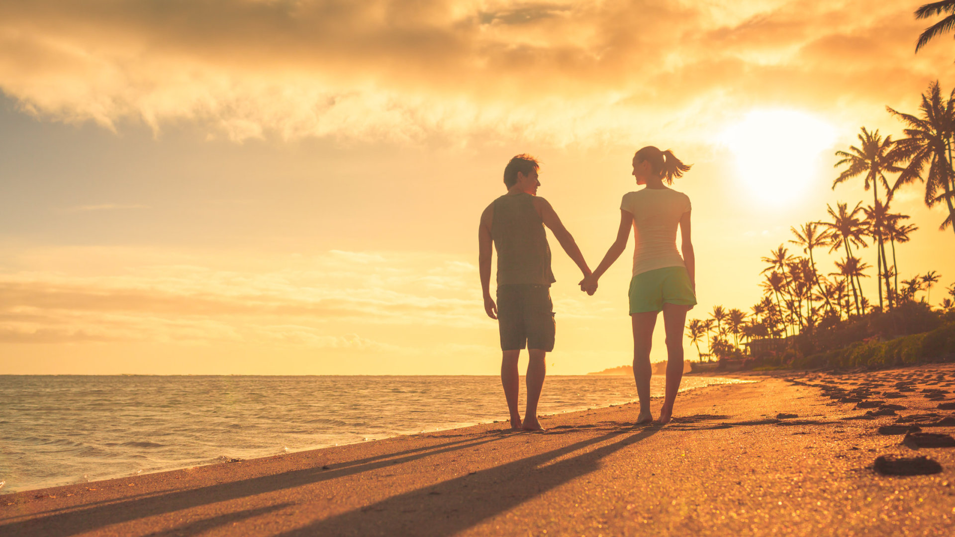 Romantic couple walking on the beach during sunset. Location Hawaii.