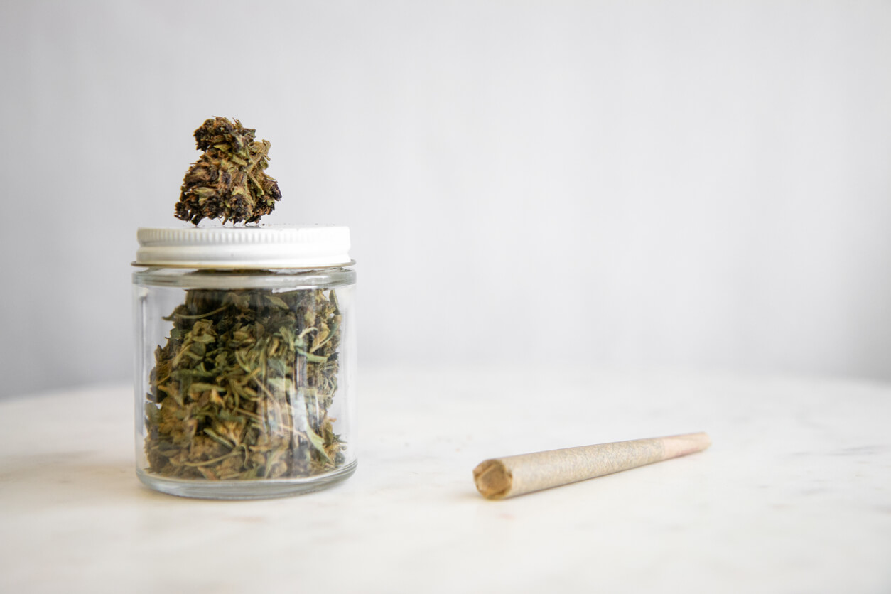 Glass jar full of Marijuana shake sits on a white marble surface with a cannabis joint next to it.